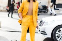 12 a bright yellow suit with flare pants, a camel top that matches the skin and a small clutch