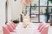 12 a pink grass overhead centerpiece and matching pink chair make the reception space very romantic