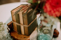 12 a vintage book wedding centerpiece on a wooden slice is a cool idea for a book-loving wedding