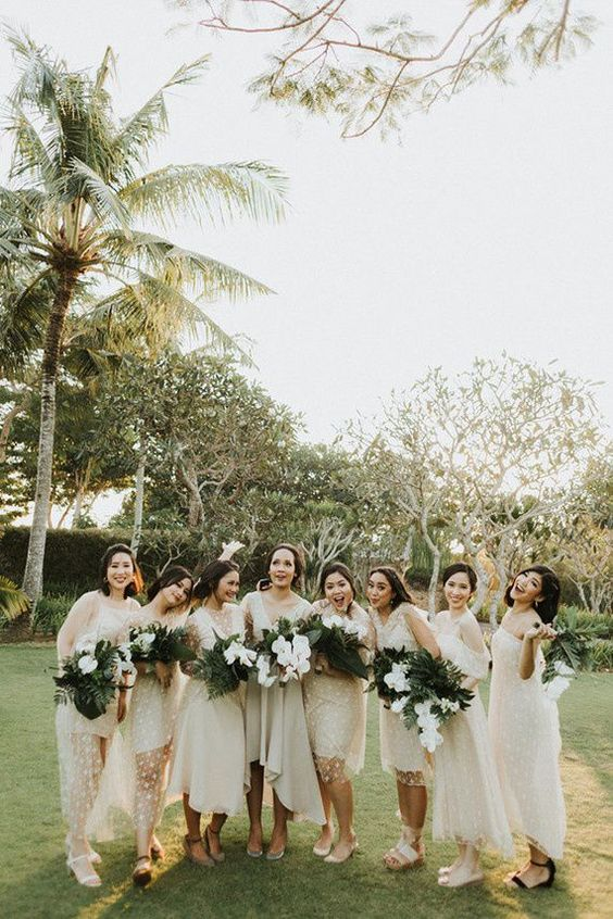 mismatching neutral midi bridesmaid dresses with polka dots and various sandals for a modern tropical wedding