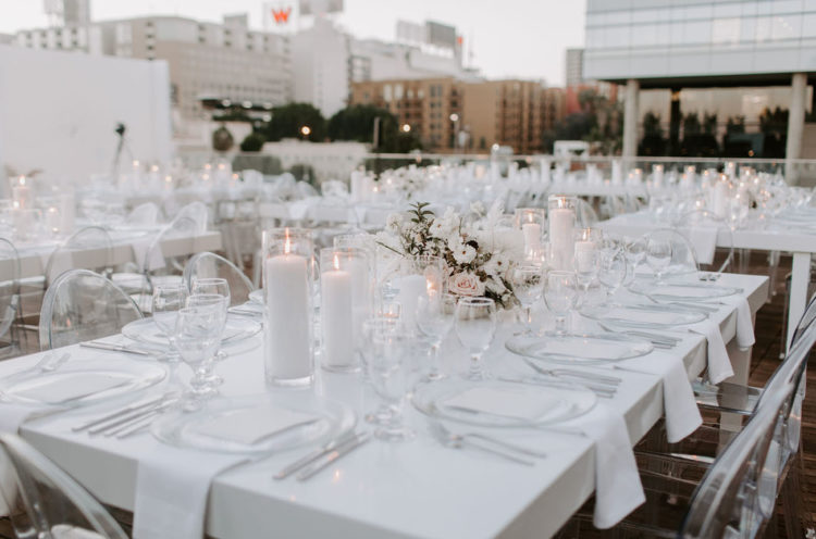 The reception tables were all-white, with candles, beautiful floral centerpieces, sheer chargers and white napkins