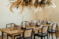 13 a stylish overhead installation of pampas grass, dried greenery and branches for a Halloween wedding