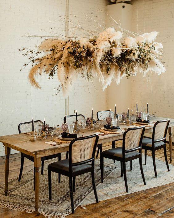 a stylish overhead installation of pampas grass, dried greenery and branches for a Halloween wedding