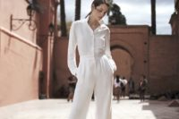 17 a white jumpsuit with wideleg pants and long sleeves requires only heels, statement earrings and a little clutch