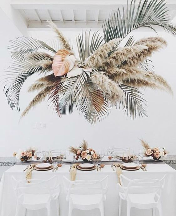 an oversized tropical wedding installation with leaves and pampas grass will make your wedding feel really tropical-like