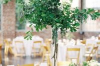 20 a lush and tall greenery centerpiece of branches and leaves is a very modern idea