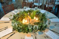 21 a greenery table centerpiece with eucalyptus, ferns and candles is a unique wreath-like piece