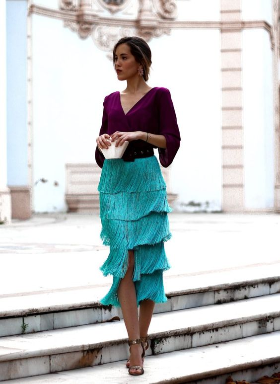 a catchy color block wedding guest outfit with a purple blouse, a turquoise fringe midi, a black belt and metallic shoes