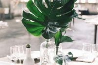 22 a modern centerpiece with clear glass vases and palm leaves is great to add a tropical touch to the table