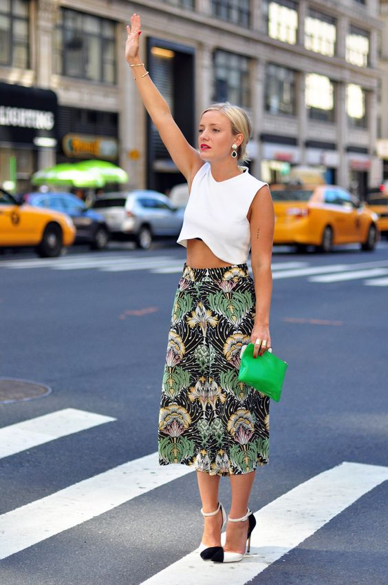 a geometric white crop top, a tropical print A line midi, blakc and white shoes and a green clutch