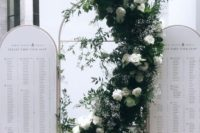 23 a modern arched seating chart with a lush greenery and white bloom installation curved between the two parts
