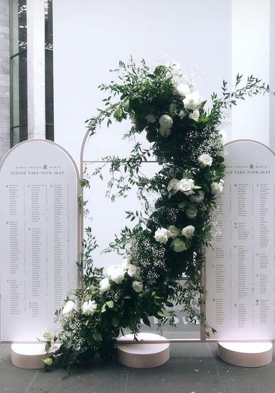 a modern arched seating chart with a lush greenery and white bloom installation curved between the two parts