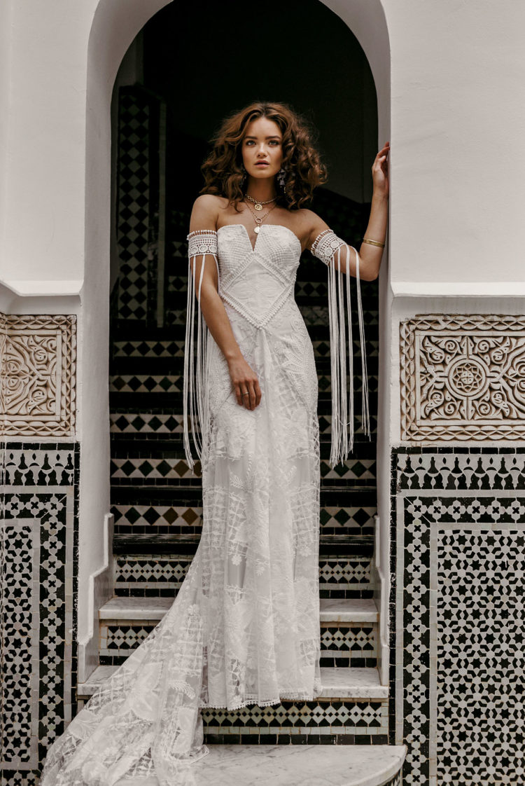boho lace wedding dress with a textural bodice, a train and lace arm band sleeves with long fringe