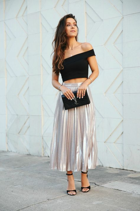 a metallic A line pleated midi, a black off the shoulder crop top, black heels and a black clutch
