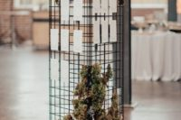 24 a modern wedding seating chart with moss, greenery and candles around is a stylish installation