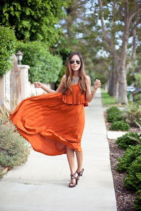 an all-pleated orange midi dress with leather sandals and a statement necklace create a bit boho