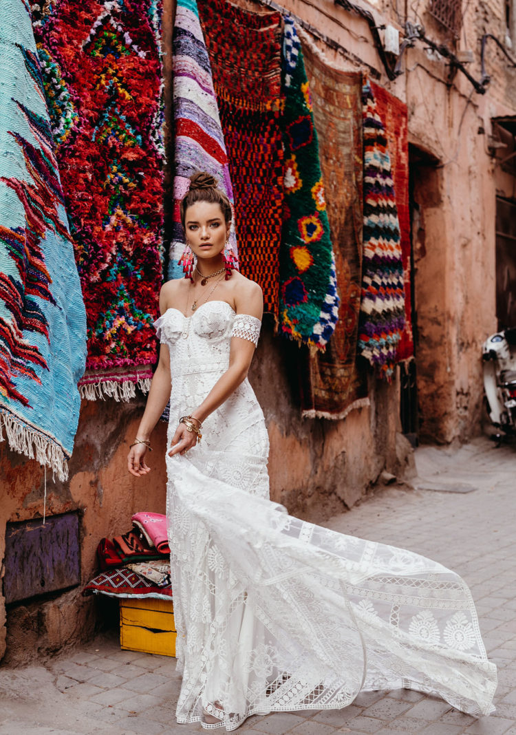 boho lace wedding gown, with a strapless neckline, a sheath silhouette, a train and arm lace bracelets