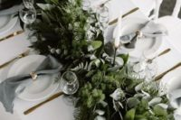 25 a lush woodland-inspired greenery table runner with various kinds of eucalyptus, moss and ferns