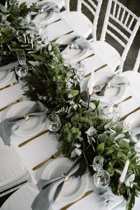 a lush woodland inspired greenery table runner with various kinds of eucalyptus, moss and ferns