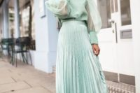 25 a mint green pleated midi skirt styled with a matching blouse with puff sleeves and floral slip mules