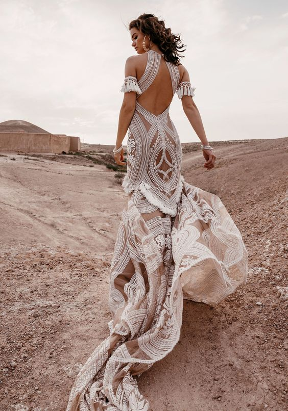 a nude white lace boho sheath wedding gown with a cutout back and tassel arm sleeve bands