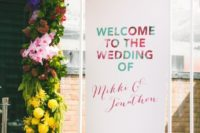 25 a welcome wedding installation with lush greenery and bright blooms plus a sign for a modern wedding