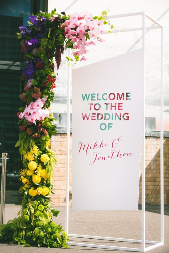 a welcome wedding installation with lush greenery and bright blooms plus a sign for a modern wedding