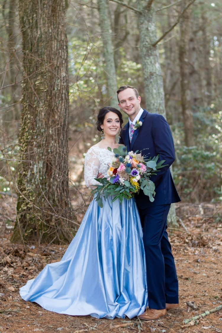 The bride was wearing a white lace off the shoulder top and a blue full skirt, the groom was wearing a bright blue suit with a colorful floral tie
