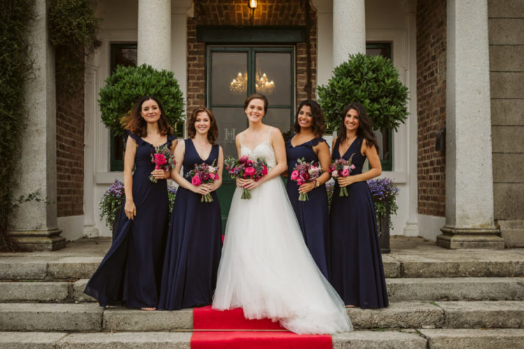 The bride was wearing an A-line wedding gown with spaghetti straps, an embellished bodice and a tulle skirt, the bridesmaids were rocking elegant navy maxi dresses