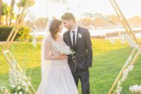 02 a beautiful hex spring wedding arch with white blooms, candles and geometric hangings with white florals