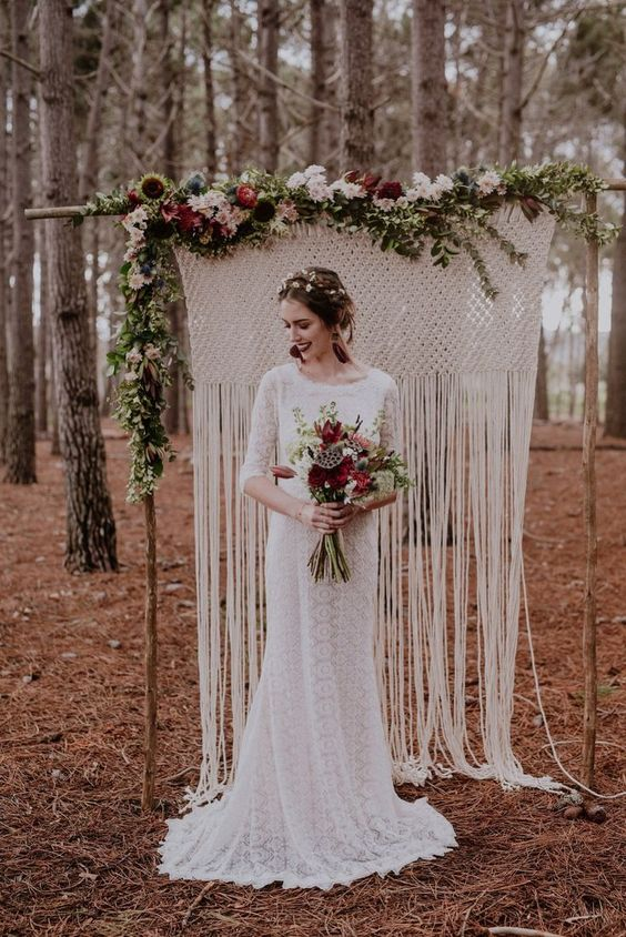 a boho fall wedding backdrop of macrame with long fringe, greenery, burgundy and white blooms on top