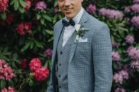 02 a checked blue three-piece suit, a white shirt, a navy polka dot bow tie plus a white floral boutonniere