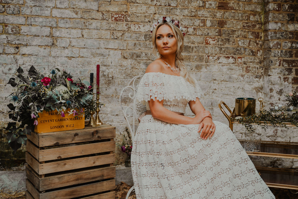 The bride was wearing a lace off the shoulder wedding dress with a statement necklace