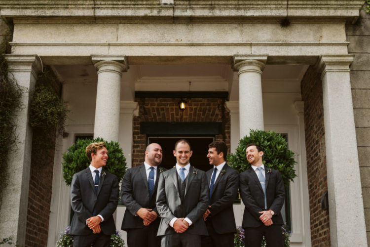 The groom was wearing a grey three-piece suit and a blue tie, and the groomsmen were rocking two-piece suits in the same color