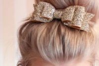 03 a large top knot highlighted with a gold glitter ribbon and a bow on top looks timeless and very chic