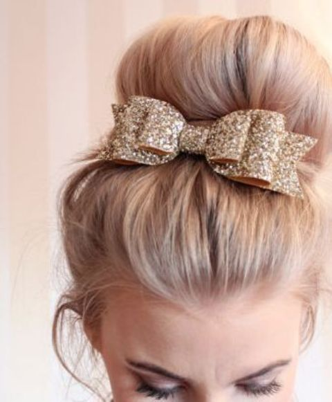 a large top knot highlighted with a gold glitter ribbon and a bow on top looks timeless and very chic