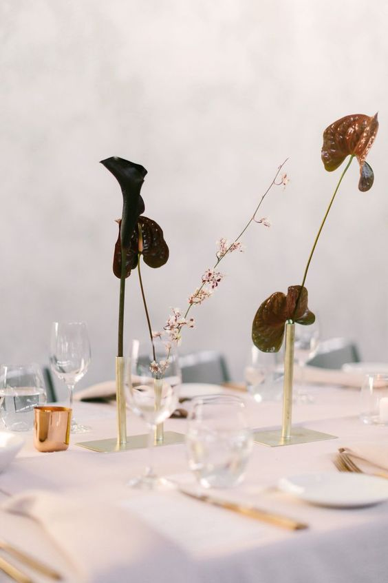 gold pipes on stands with very dark calla lilies are a minimalist and moody centerpieces that look really wow