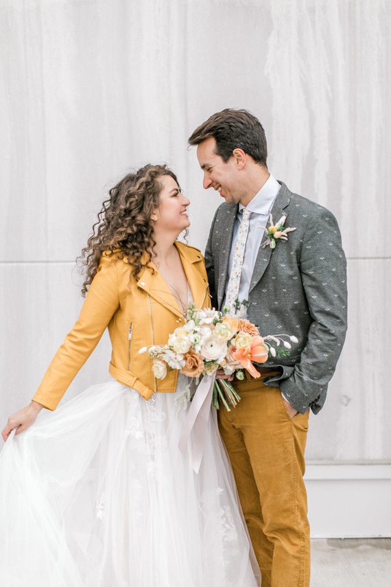 The bride covered up with a marigold leather jacket, the groom was wearing a grey jacket with a bee print, marigold pants and a floral tie