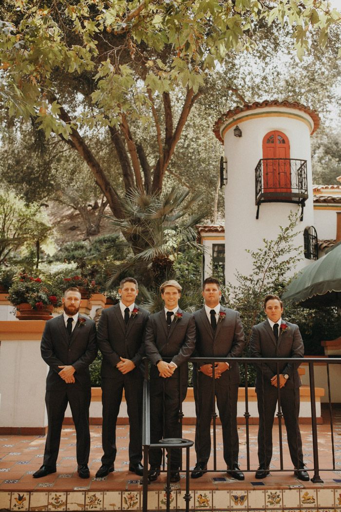 The groom and groomsmen were rocking grey three-piece wedding suits with black ties and burgundy boutonnieres