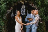 04 The wedding arch was done with greenery and blooms, with lace dream catchers and feathers for a boho feel
