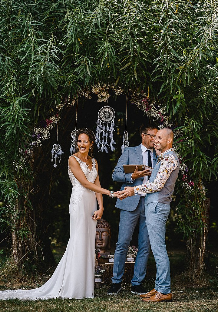 The wedding arch was done with greenery and blooms, with lace dream catchers and feathers for a boho feel