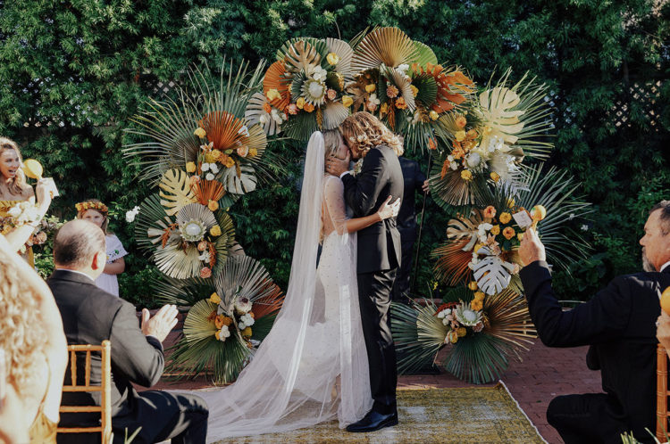 The wedding arch was done with king proteas and tropical leaves, usual and spray painted