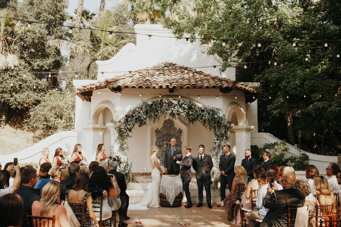 The wedding arch was done with lush greenery and burgundy blooms plus an altar with fringe