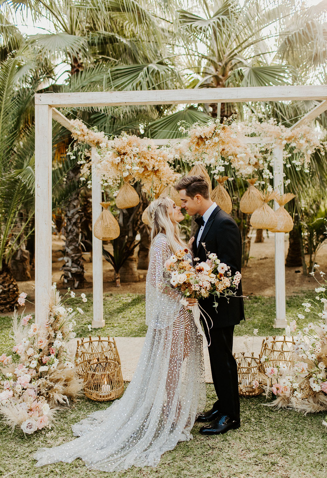 The wedding ceremony space was done with an arch decorated with neutral and white blooms, some lanterns hanging and floor ones, pampas grass and blush blooms