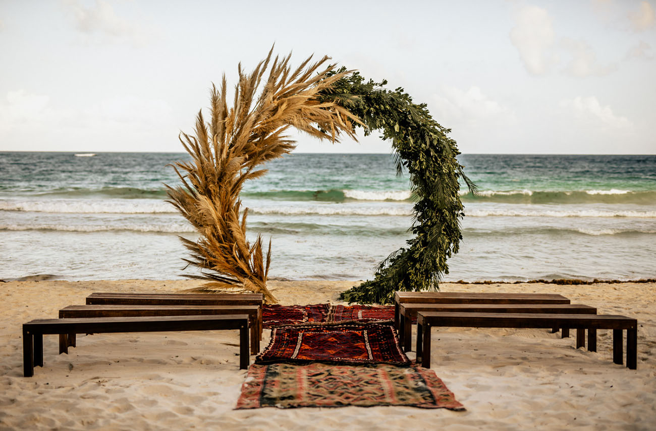 The wedding ceremony space was done with benches, boho rugs and a large circle wedding arch of pampas grass and greenery