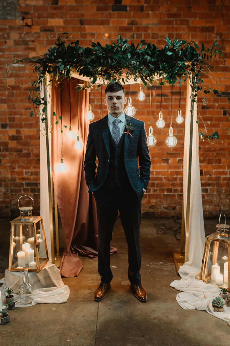 a navy windowpane print three-piece suit, a white shirt, a printed tie and brown shoes for a vintage-inspired groom's look