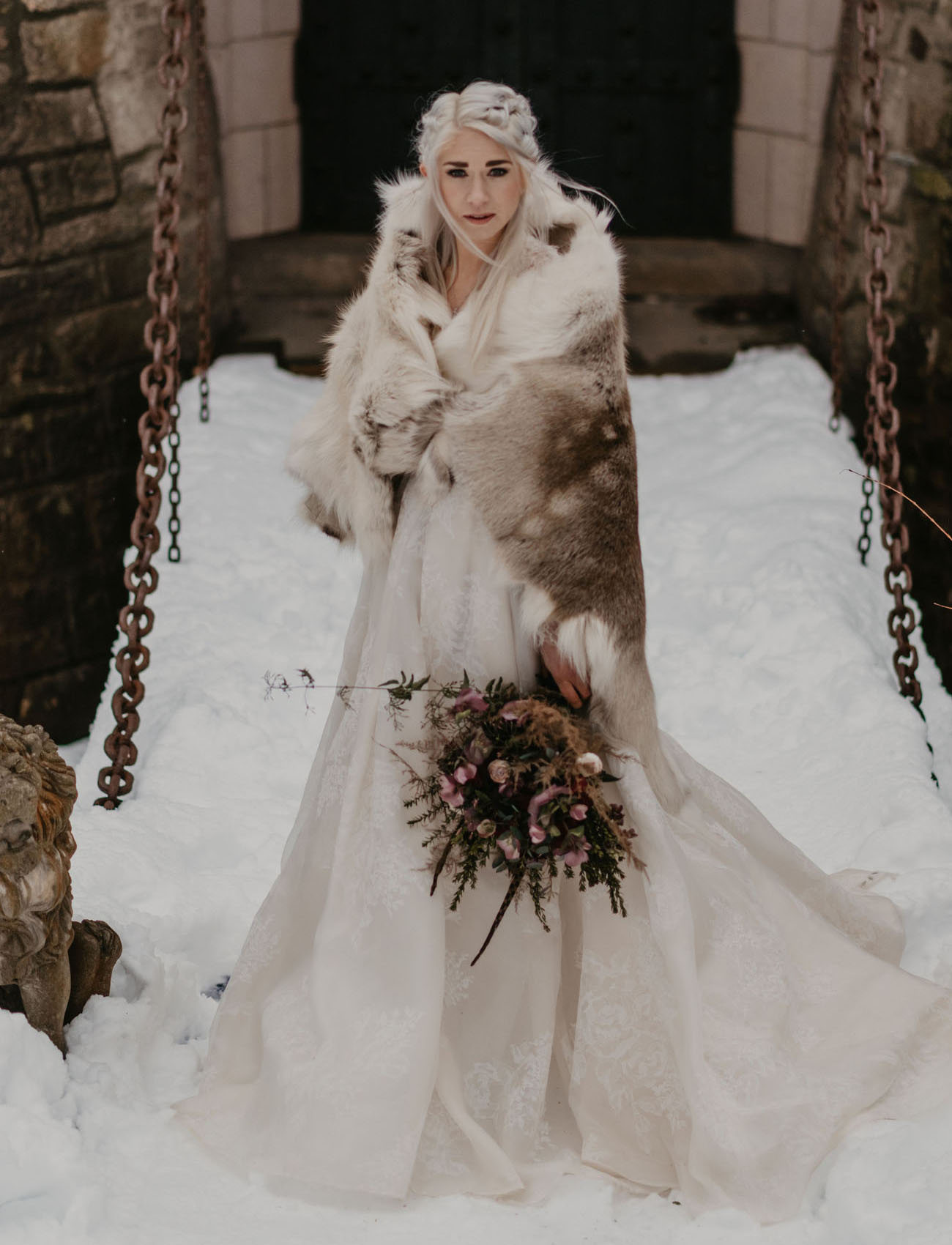 Daenerys styled bride in a lace wedding ballgown, with a braided hairstyle and a fur coverup