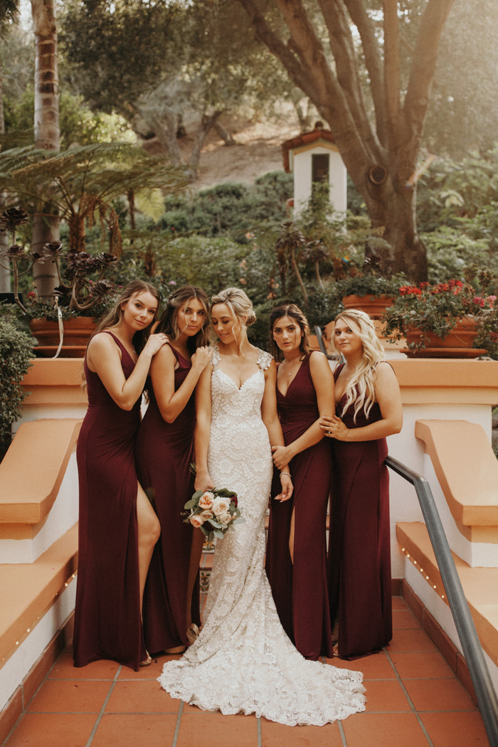 The bridesmaids were wearing burgundy wide strap maxi dresses with V-necklines
