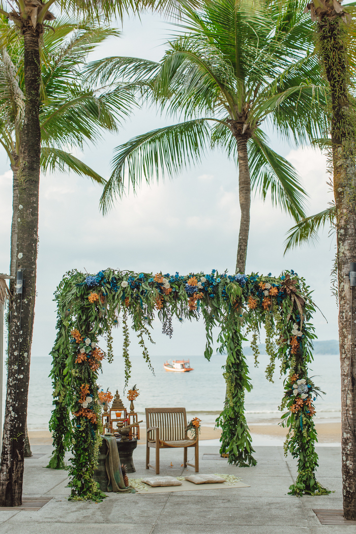 The wedding arch was created almost on the beach, it was decorated with greenery, bright rust and blue blooms