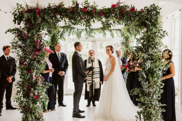 The wedding arch was done with lush greenery and bright fuchsia and bold red florals